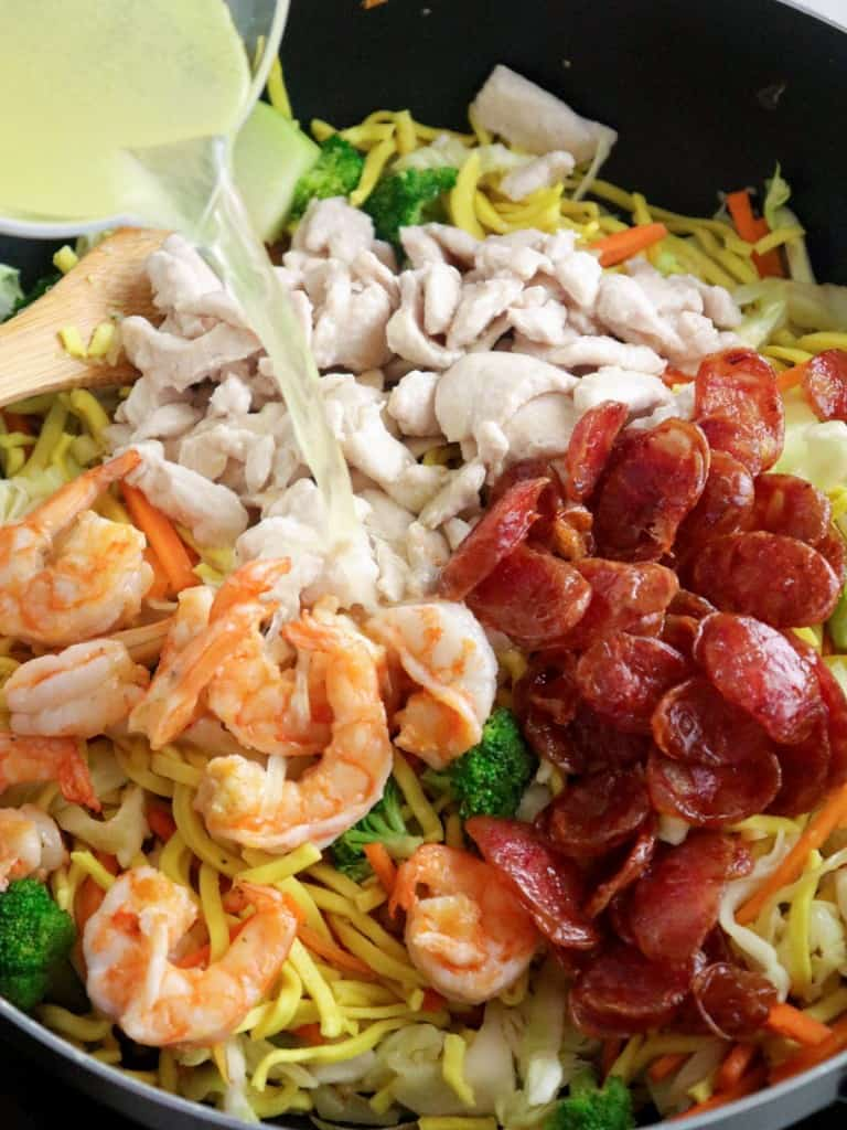 adding chicken broth to shrimp, Chinese sausages, chicken, assorted veggies and noodles in a skillet