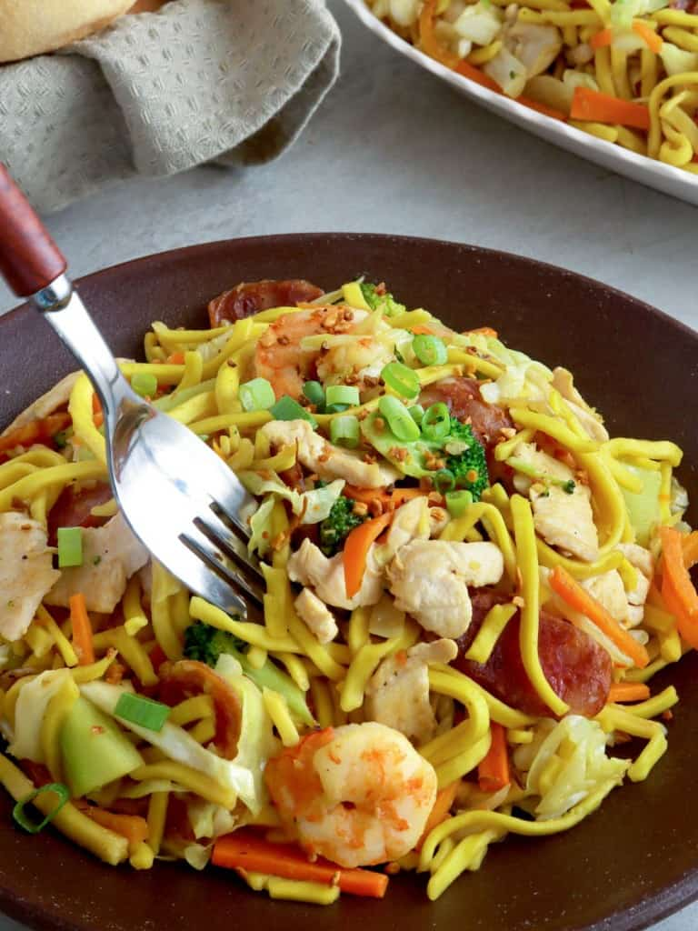 serving pancit lomi guisado with a fork from a plate