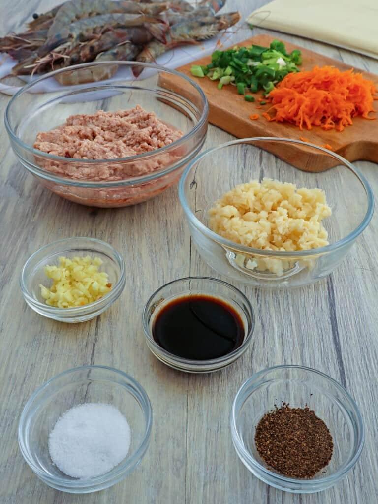 shrimp, ground pork, water chestnuts, garlic, soy sauce, pepper, shredded carrots, chopped green onions