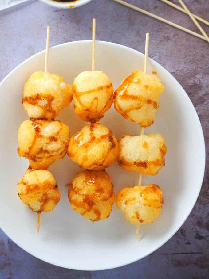tungi-tungi rice balls in bamboo sticks on a white plate