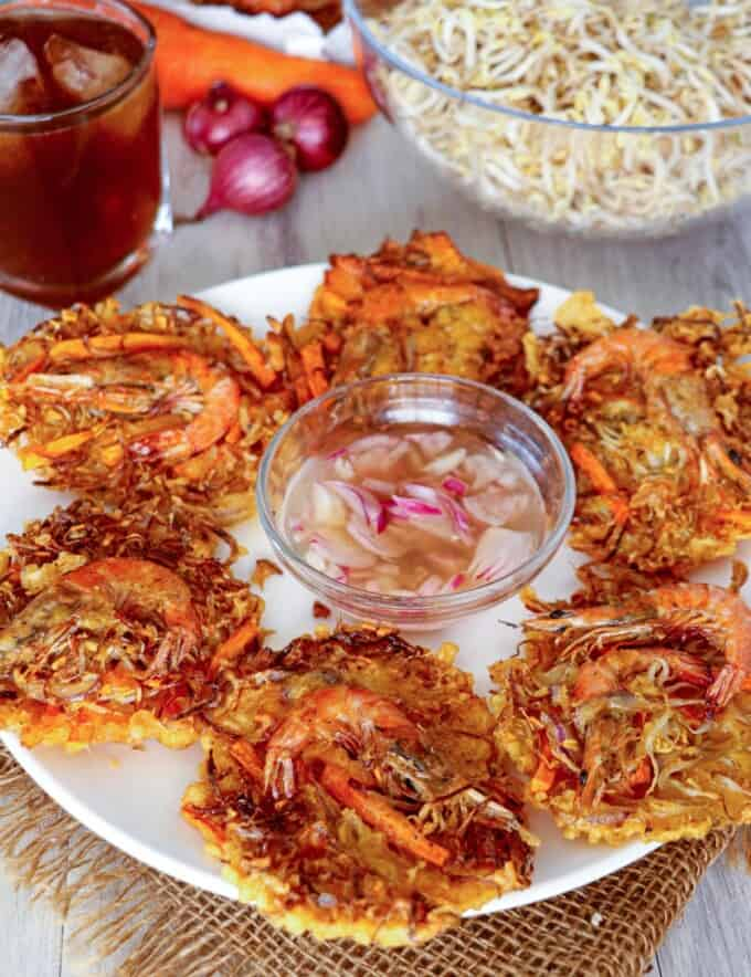 Shrimp and Vegetable fritters on a white plate with a bowl of spicy vinegar