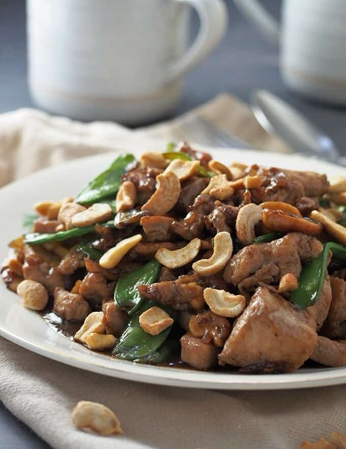 chicken with cashew nuts and snow peas in a white serving platter