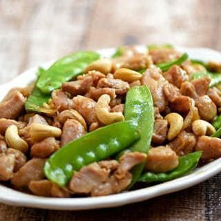 cashew chicken with snow peas on a wide serving platter