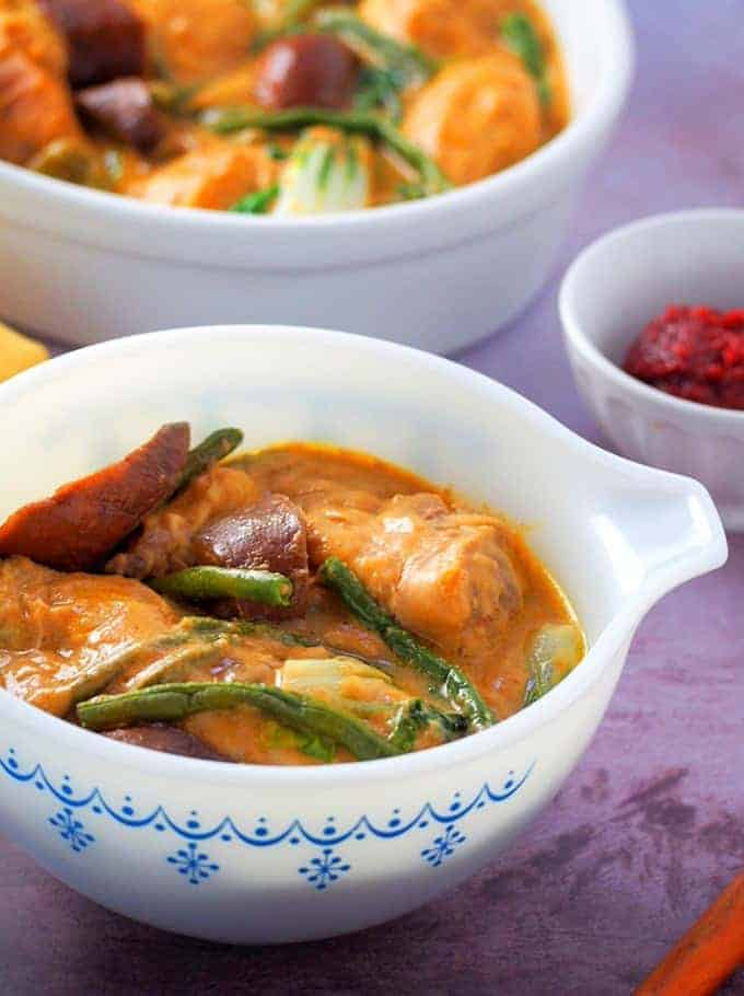 kare-kareng manok in a white serving bowl with ginisang alamang on the side