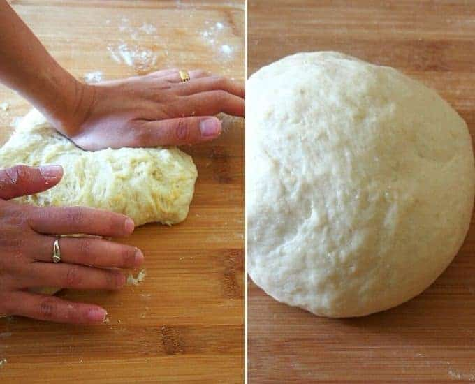 kneading bread dough with hands on a floured wood board