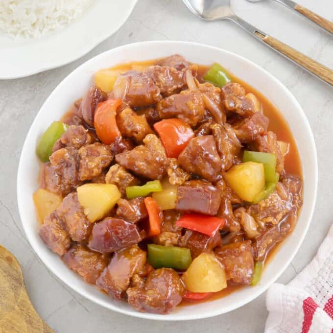 Sweet and Sour Pork in a serving bowl with a plate of steamed rice on the side