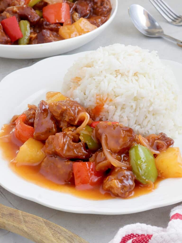 crispy pork with pineapple glaze on a white plate with steamed rice