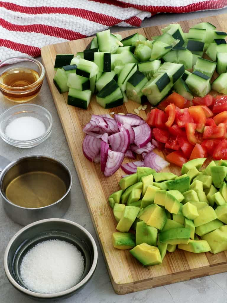 diced cucumbers, red onions, tomatoes, cucumbers on a wooden board with bowls of sugar, salt, pepper, and sesame oil on the side
