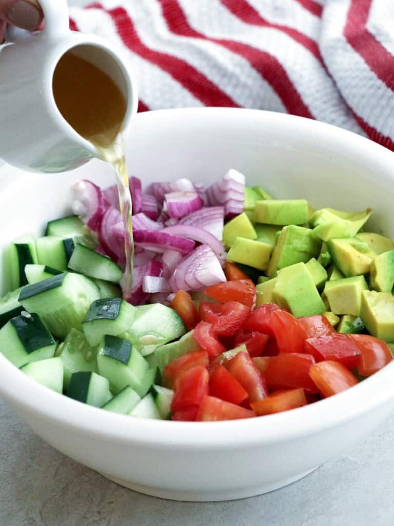 pouring rice vinegar dressing on diced cucumber, tomatoes, avocados, and red onions