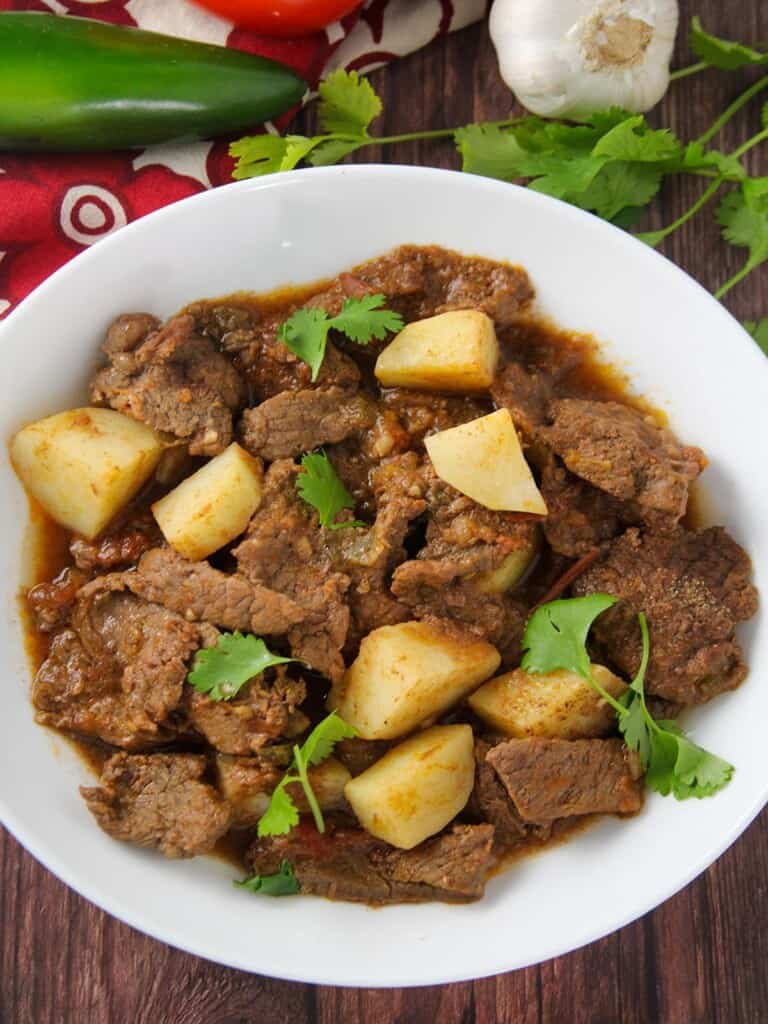Mexican-style braised beef and potatoes in tomato sauce stew in a serving bowl
