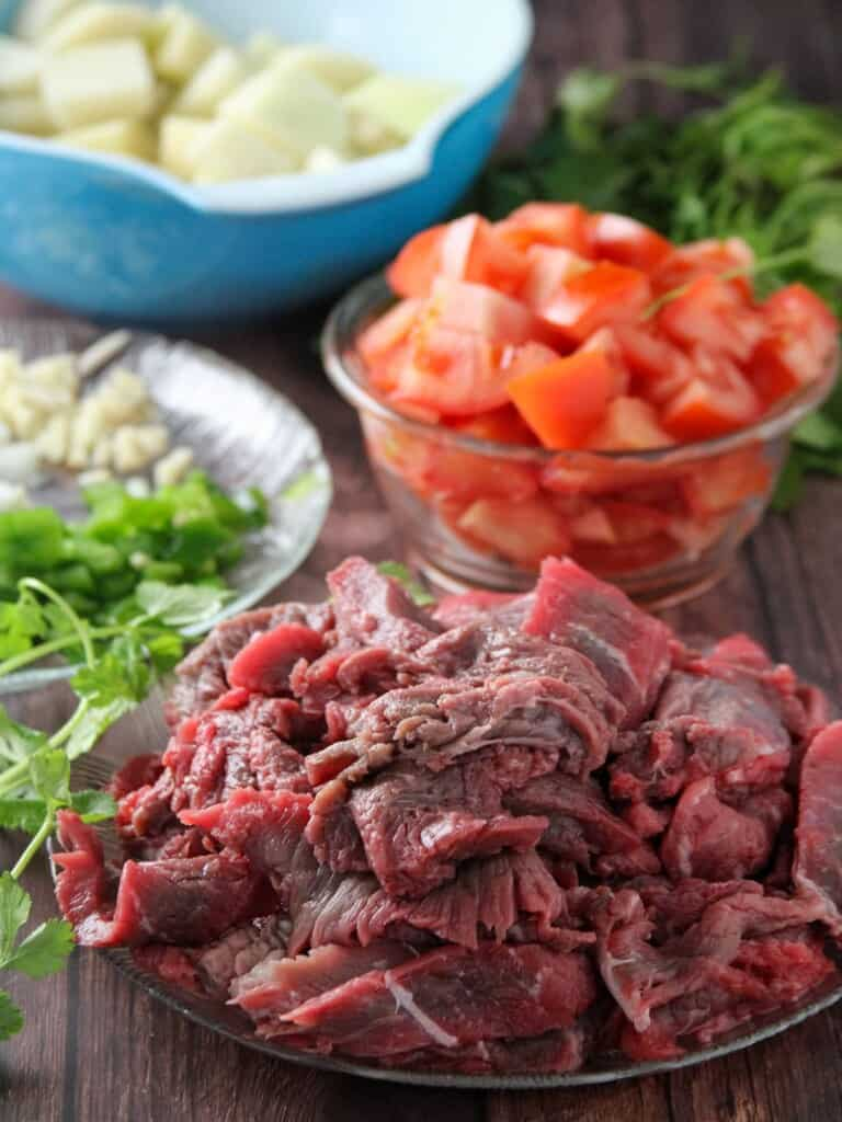 sliced beef, chopped tomatoes, potatoes, garlic, onions, jalapeno peppers