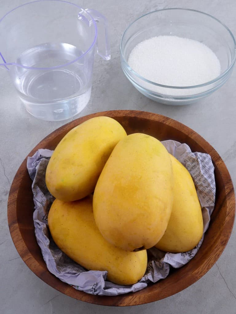 Manila mangoes in a brown bowl with a a glass of water and a bowl of sugar on the side