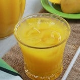 mango juice in a clear glass with pitcher on the side