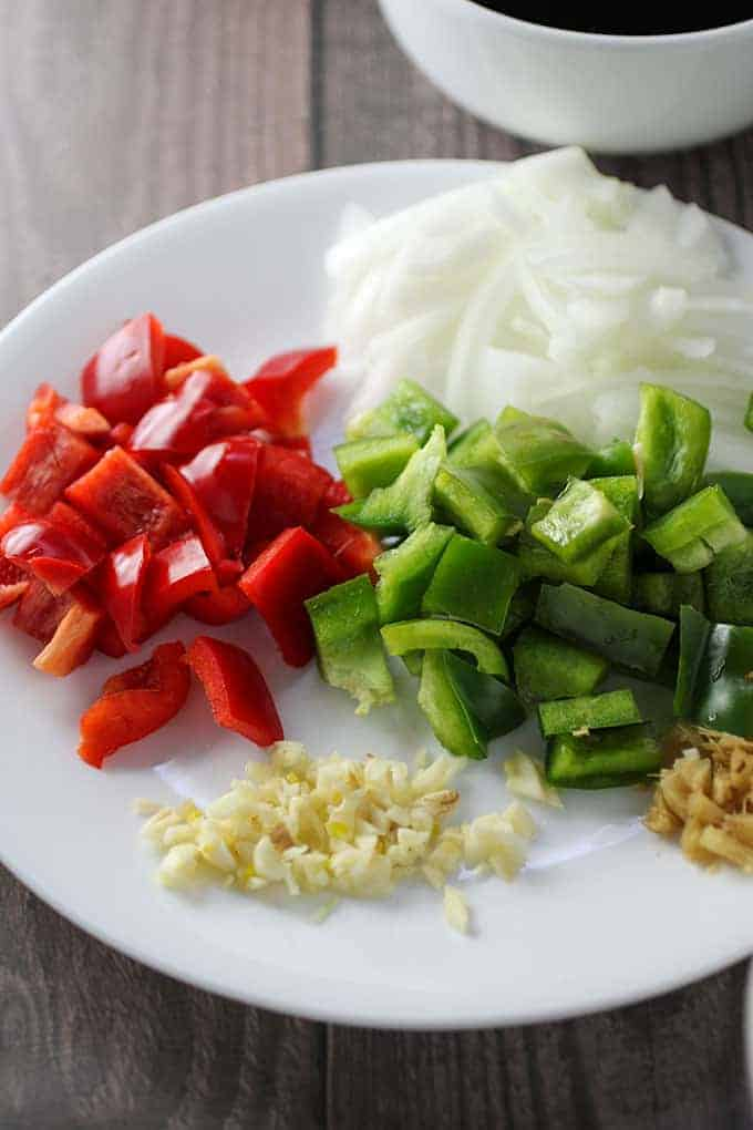 diced bell peppers, chopped onions, minced garlic on a white plate
