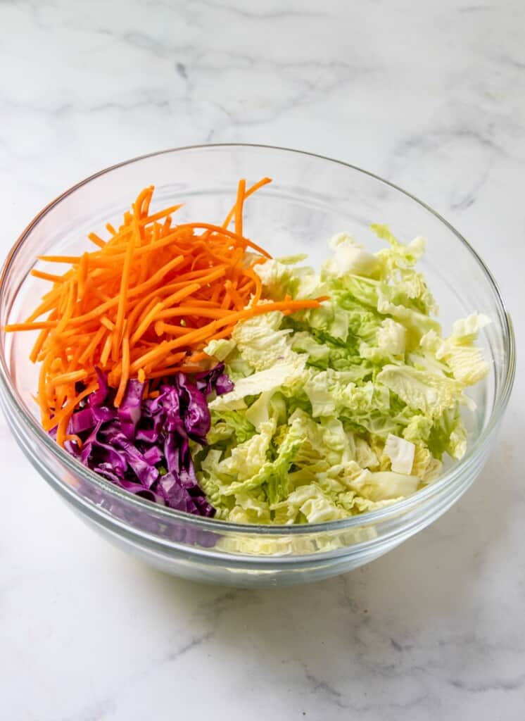 shredded napa cabbage,  carrots, red cabbage in a glass bowl