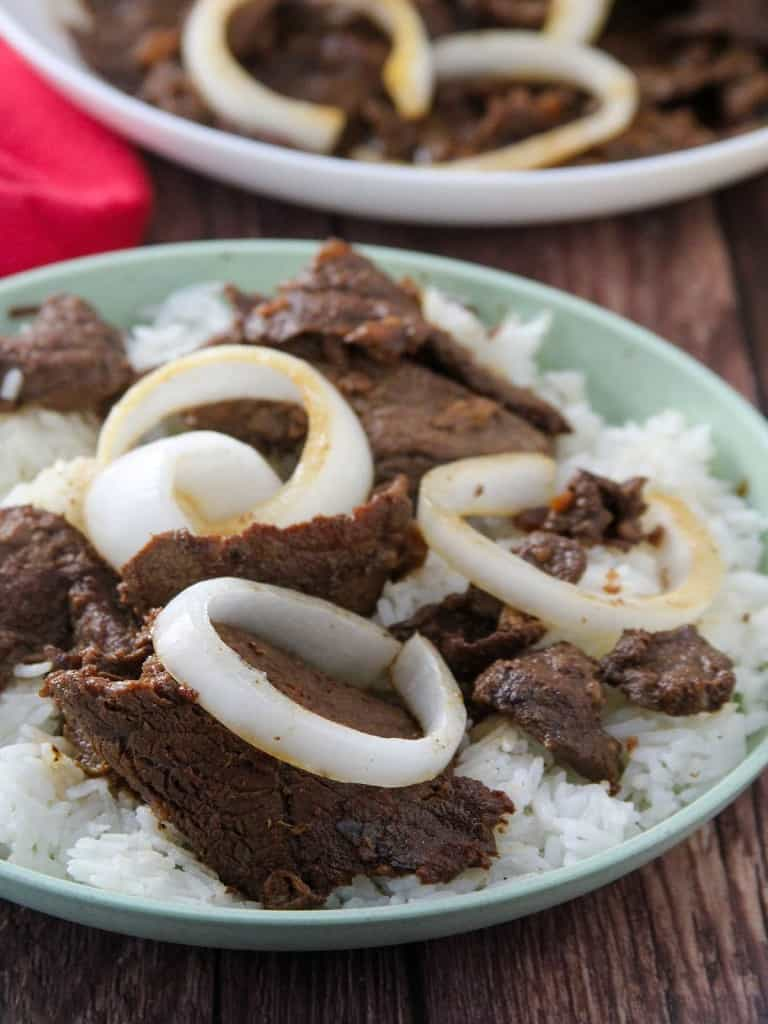 bistek Tagalog with onions over rice on a serving plate