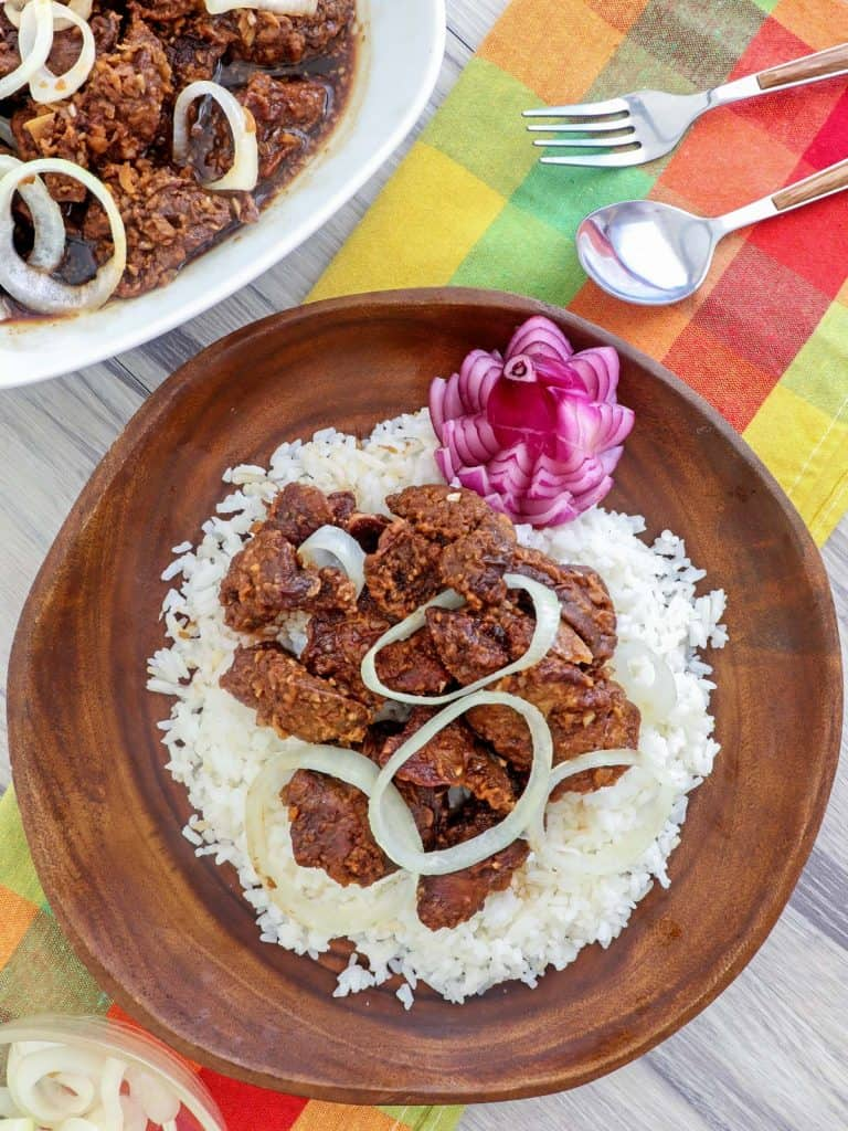 cirspy fried chicken livers with onions over rice on a wooden plate