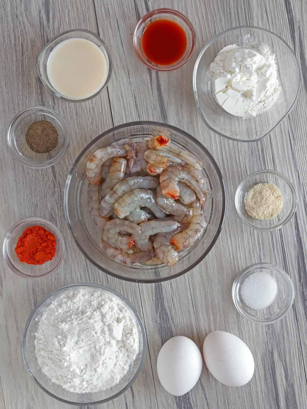 peeled shrimp, cornstarch, flour, eggs, seasonings, and milk in individual glass bowls