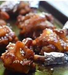 chicken lollipops with plum sauce on a baking sheet