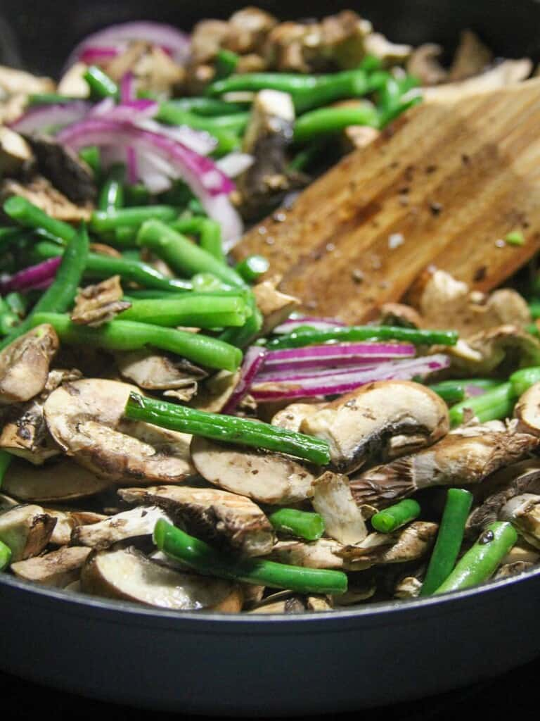 stir-frying green beans and sliced mushrooms in a wide pan
