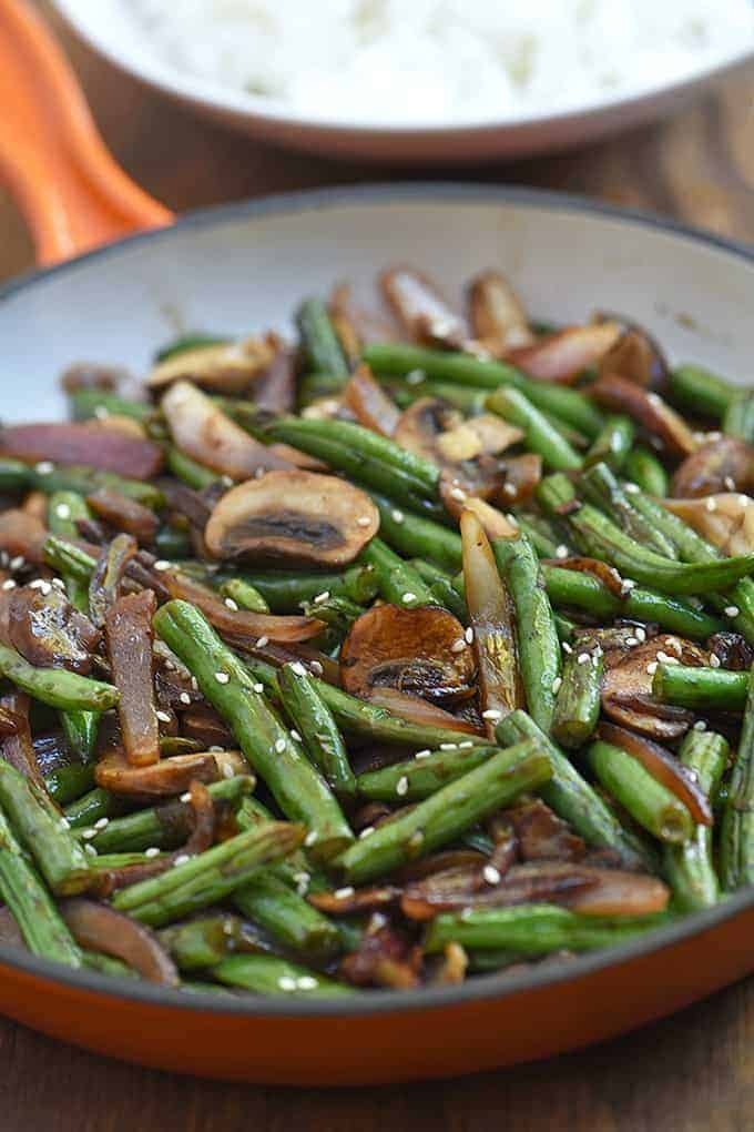 green bean stir-fry with mushrooms and onions in a orange skillet