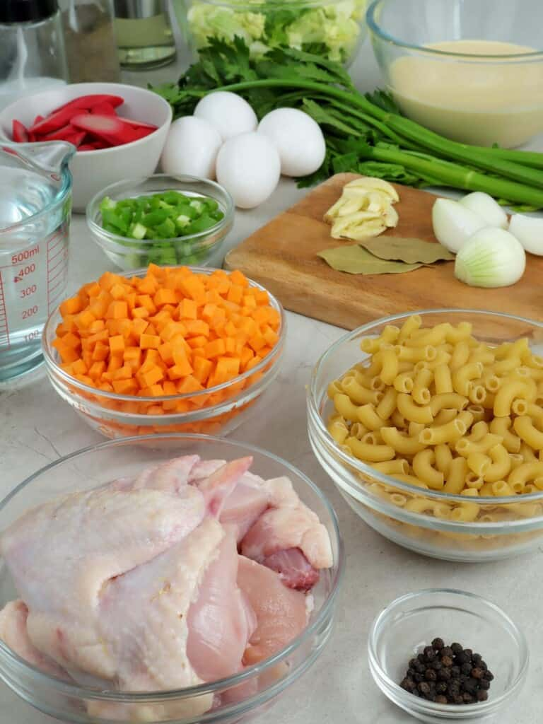 cry macaroni pasta, chicken, celery, diced carrtos, eggs, water, hot dogs, garlic, onions, bay leaves, evaporated milk