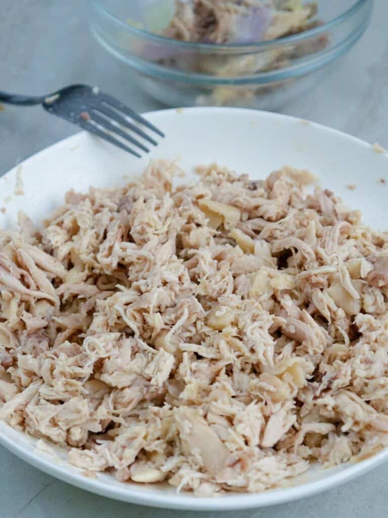 flaked chicken in a white bowl