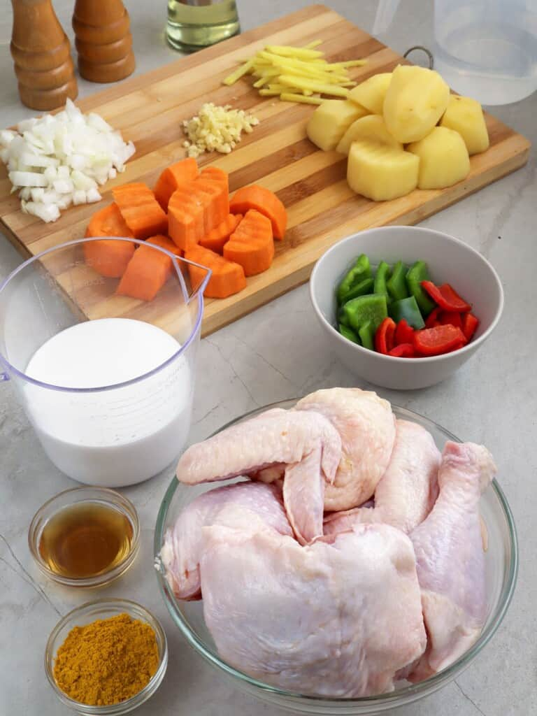 cut up bone-in chicken, peeled and cubed potatoes and carrots, coconut milk, curry powder, bell peppers