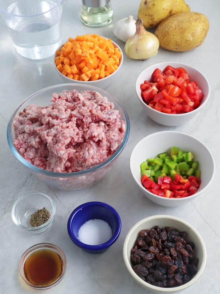 ground pork, diced bell peppers, chopped fresh tomatoes, diced carrots, potatoes, salt, peppers, raisins in individual bowls