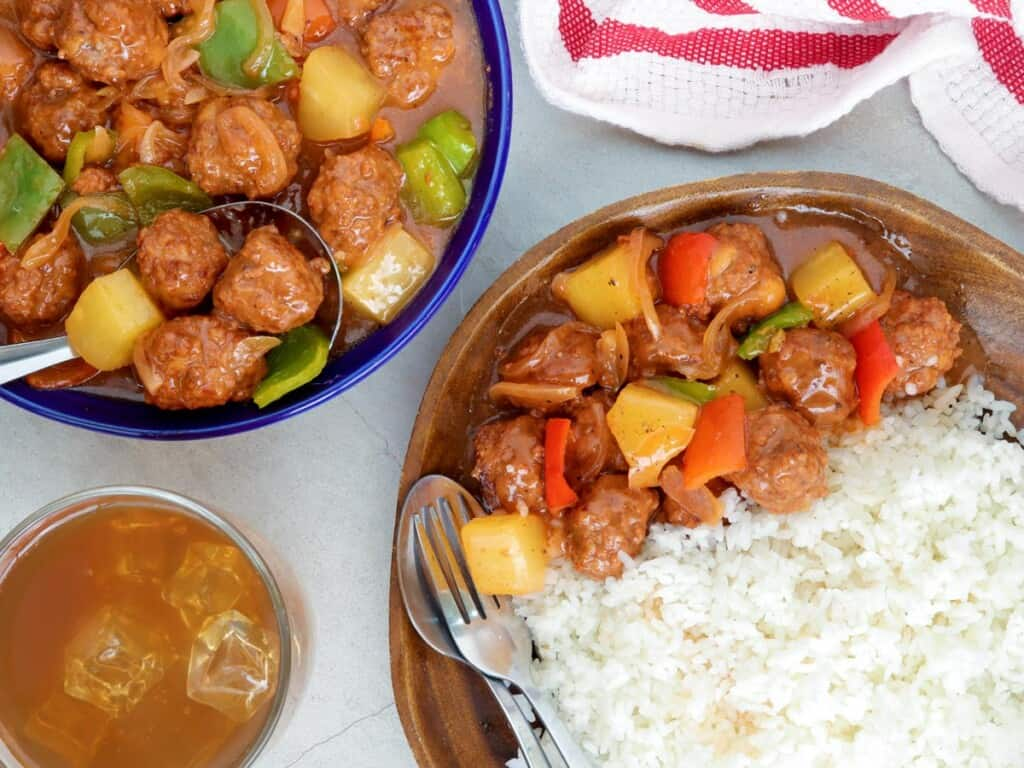 sweet sour meatballs with steamed rice on a wooden plate