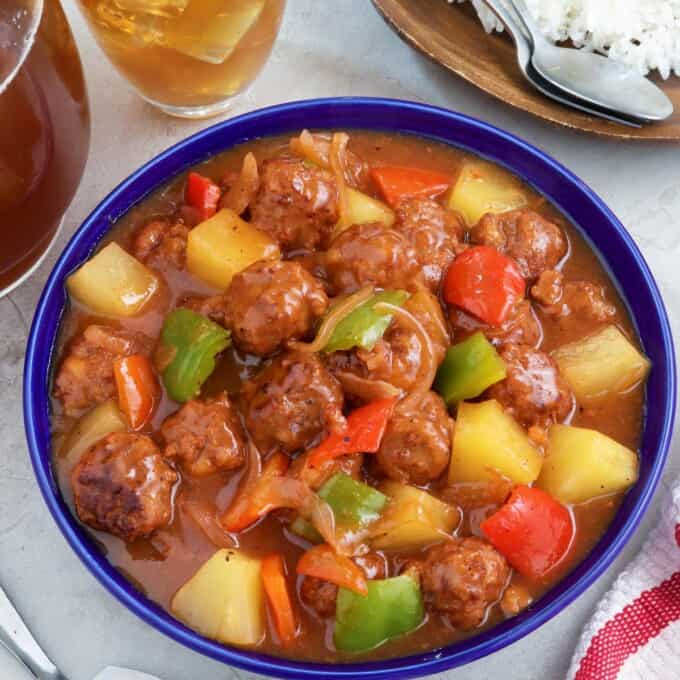 Sweet and Sour Meatballs with bell peppers and pineapples in a a blue bowl with a plate of steamed rice on the side