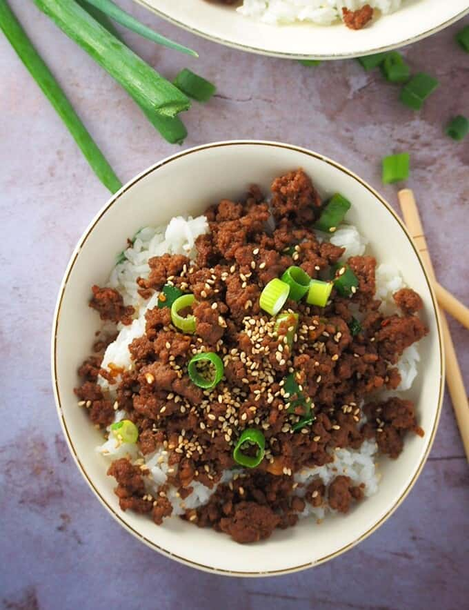 top view of Korean ground beef rice bowl with green onions and sesame seeds