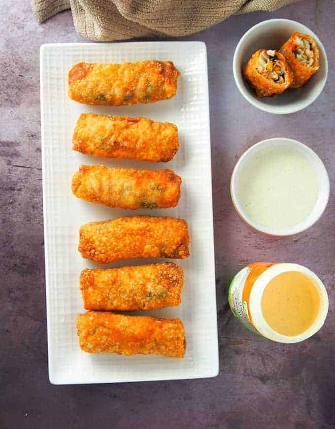 top view of southwestern chicken egg rolls on a white platter with dipping sauce on the side