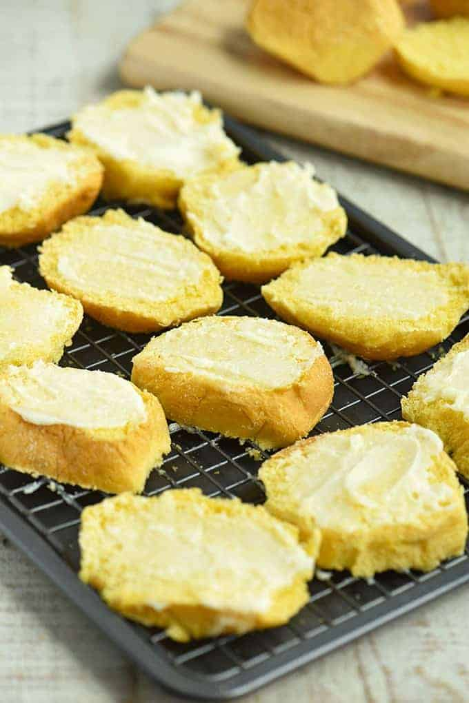 sliced pandesal with butter and sugar spread on a baking rack to bake into biscocho