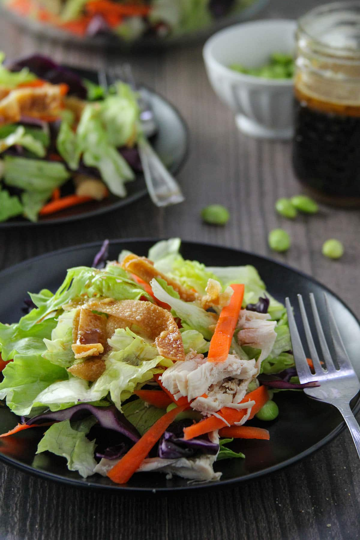Chinese Chicken Salad on a black serving plates with salad dressing on the side