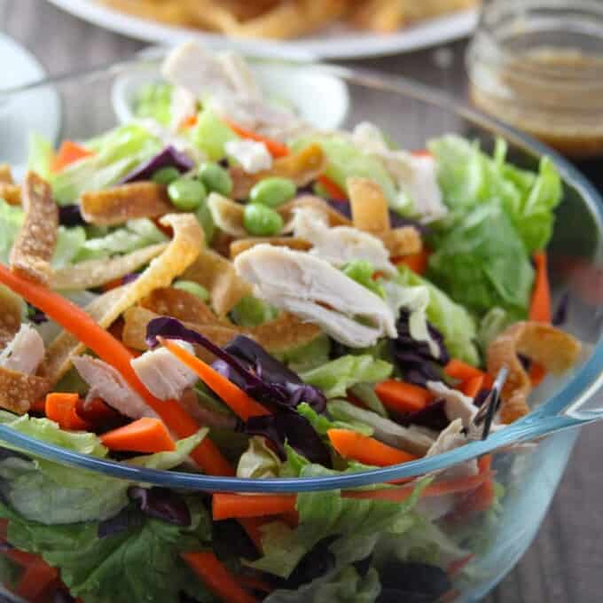 Chinese Chicken Salad in a large glass bowl with a plate of salad and a jar of dressing on the side