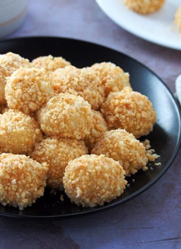 Sticky Rice Balls coated with peanuts on a black plate