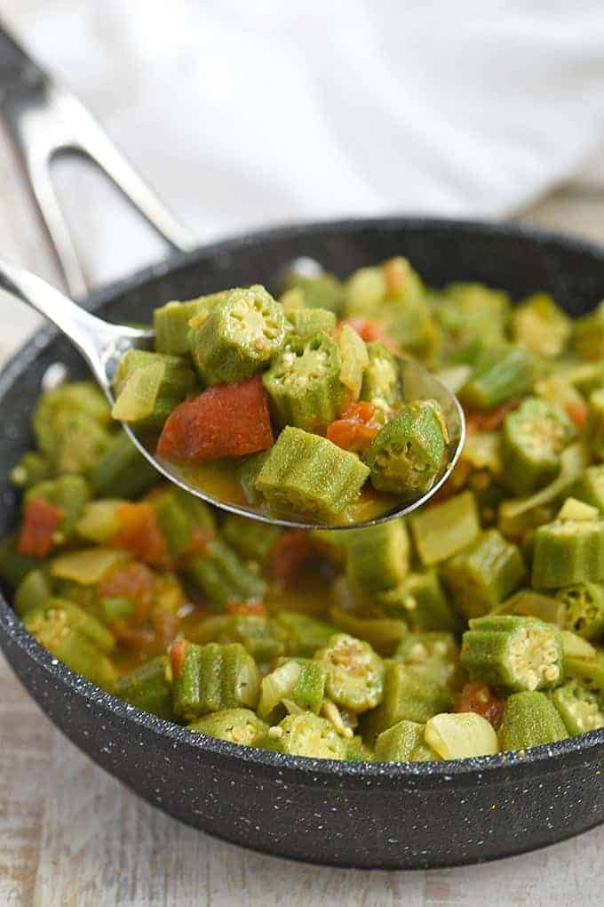 serving smothered okra and tomatoes with a serving spoon from a skillet