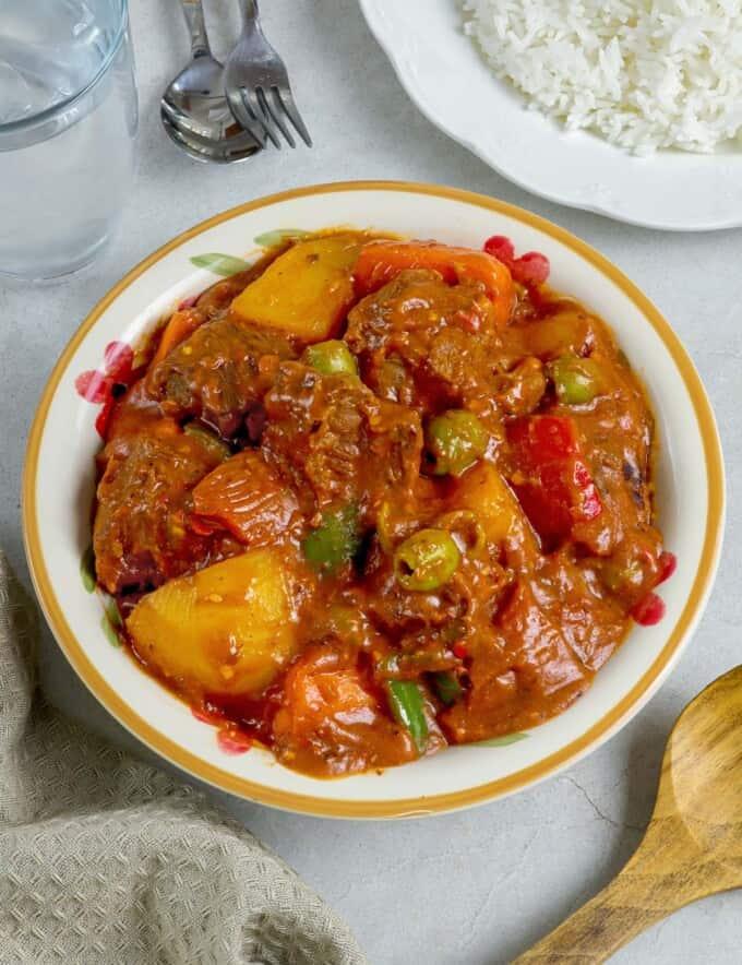 kalderetang baka in a white serving bowl