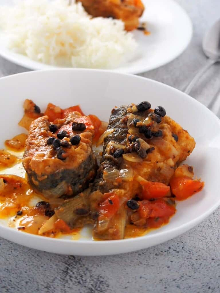 bangus with tausi and tomatoes on a white serving dish with a side of steamed rice