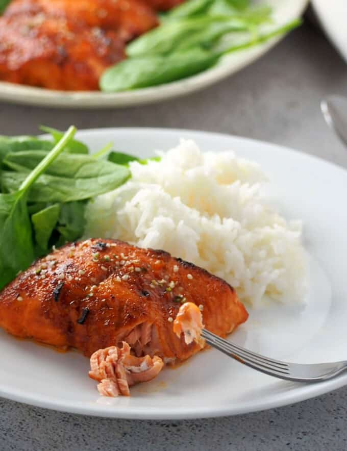 broiled salmon with hoisin glaze on a white plate with a side of steamed rice and fresh spinach