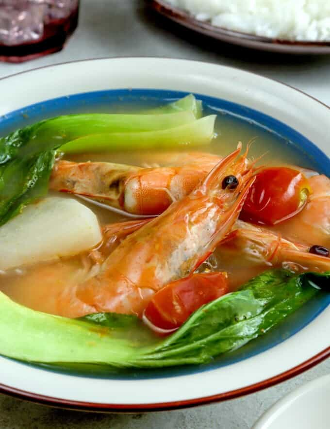 sinigang na hipon with pak choi, radish, and calamansi in a white serving bowl with a side of steamed rice