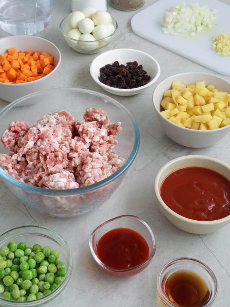 ground pork, diced carrots, diced potatoes, green peas, raisings, tomato sauce, banana ketchup, quail eggs in individual bowls