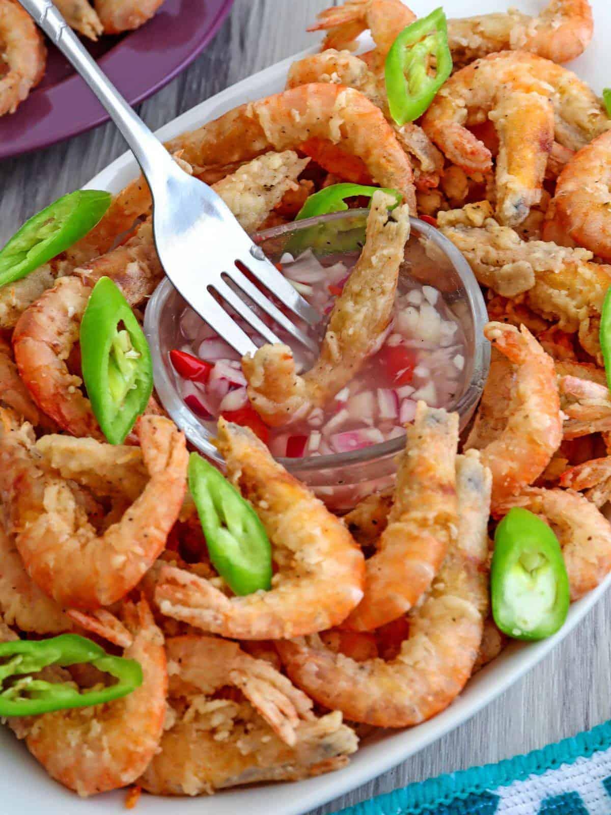 dipping crispy fried drunken shrimp in spicy vinegar