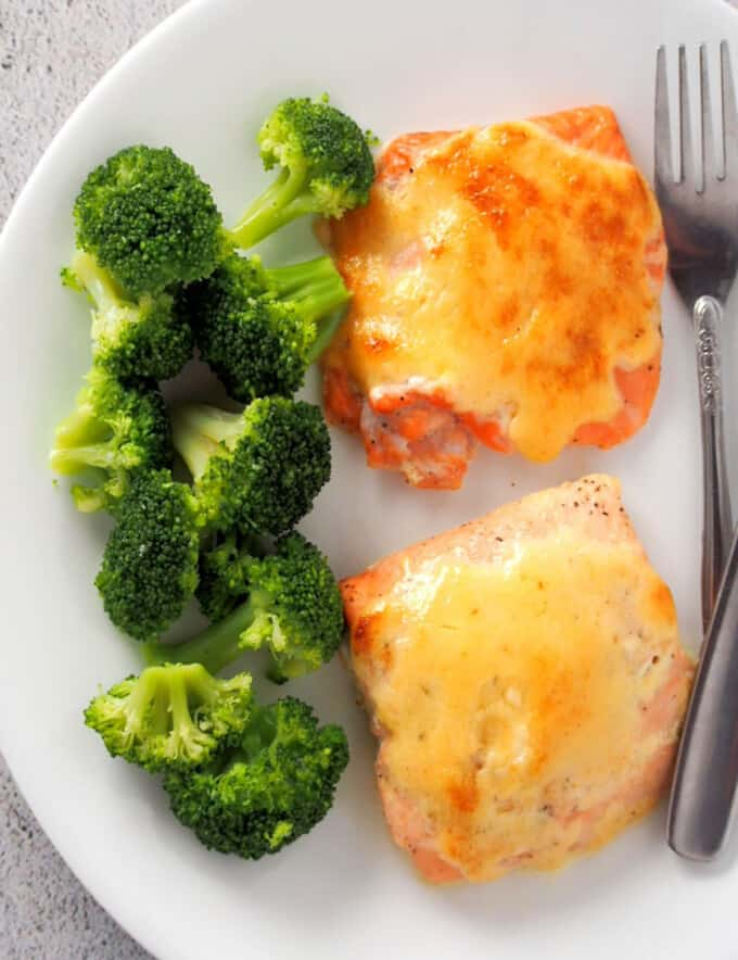 top view of baked salmon with tamarind mayo topping on white plate with steamed broccoli florets