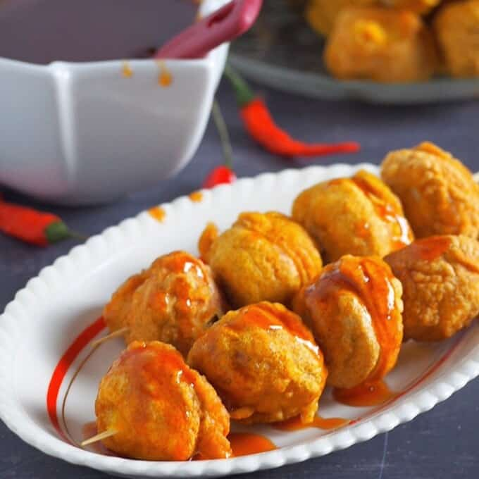 kwek-kwek on bamboo sticks on a white platter with dipping sauce on the side