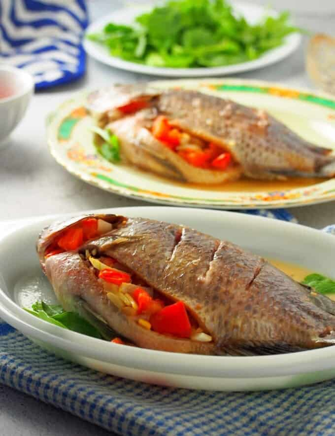 Filipino-style oven-baked tilapia stuffed with tomatoes and onions on a white serving platter