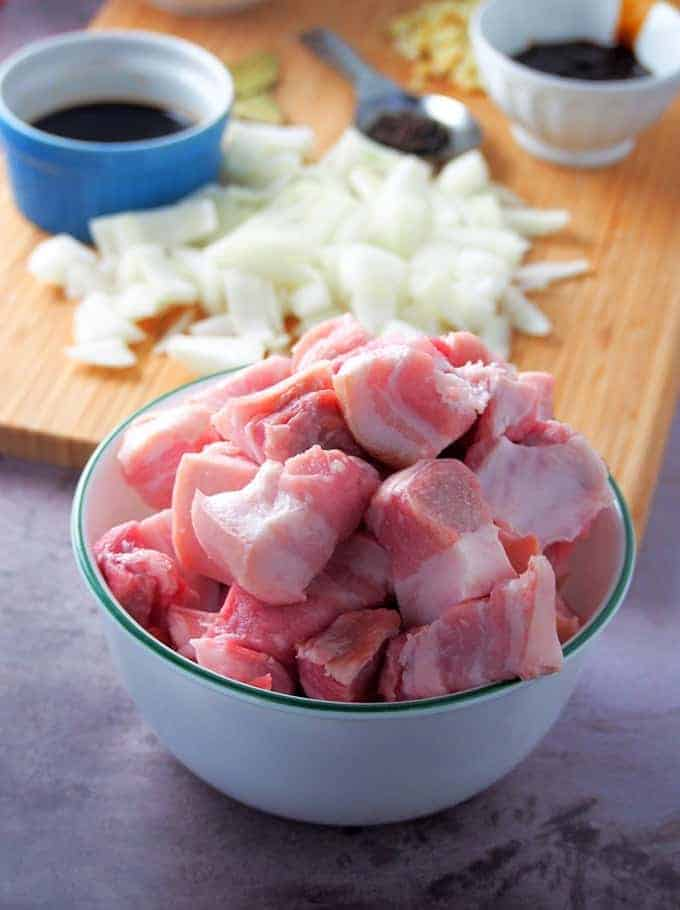cubed pork belly in a white bowl with a cutting board with chopped onions and garlic on the side