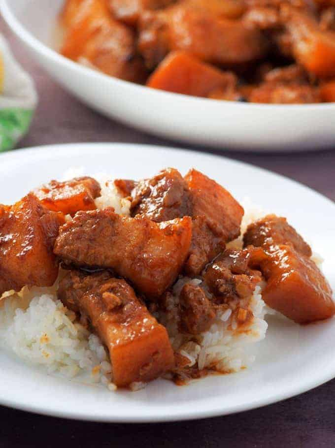 Pork Adobo with Oyster Sauce over steamed rice on a white plate