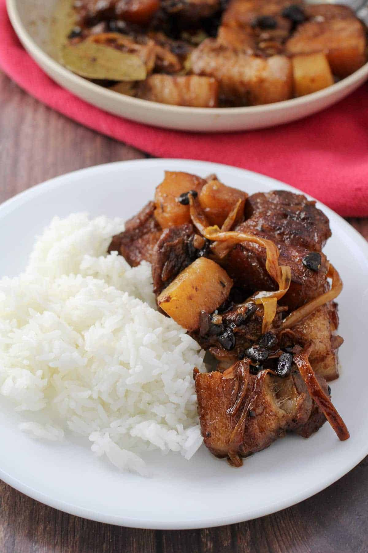 pork humba over steamed rice on a plate